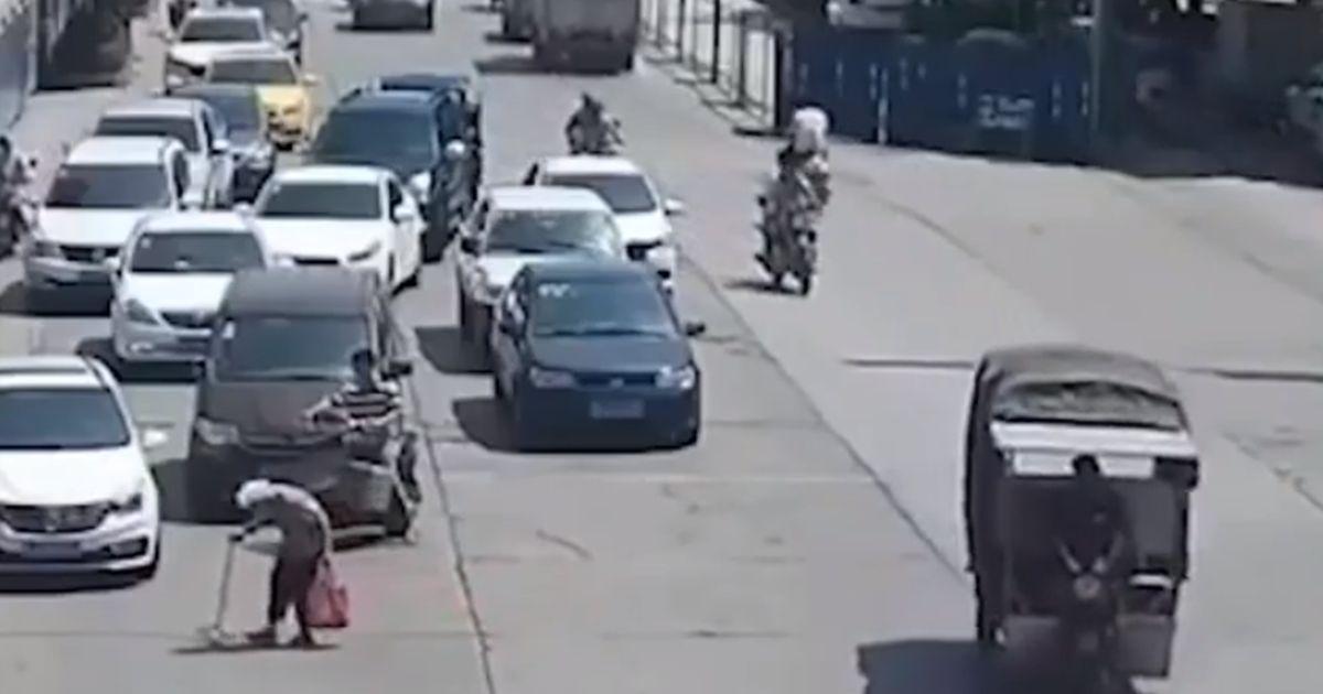 Anziana signora attraversa la strada lentamente, motociclista ferma il traffico