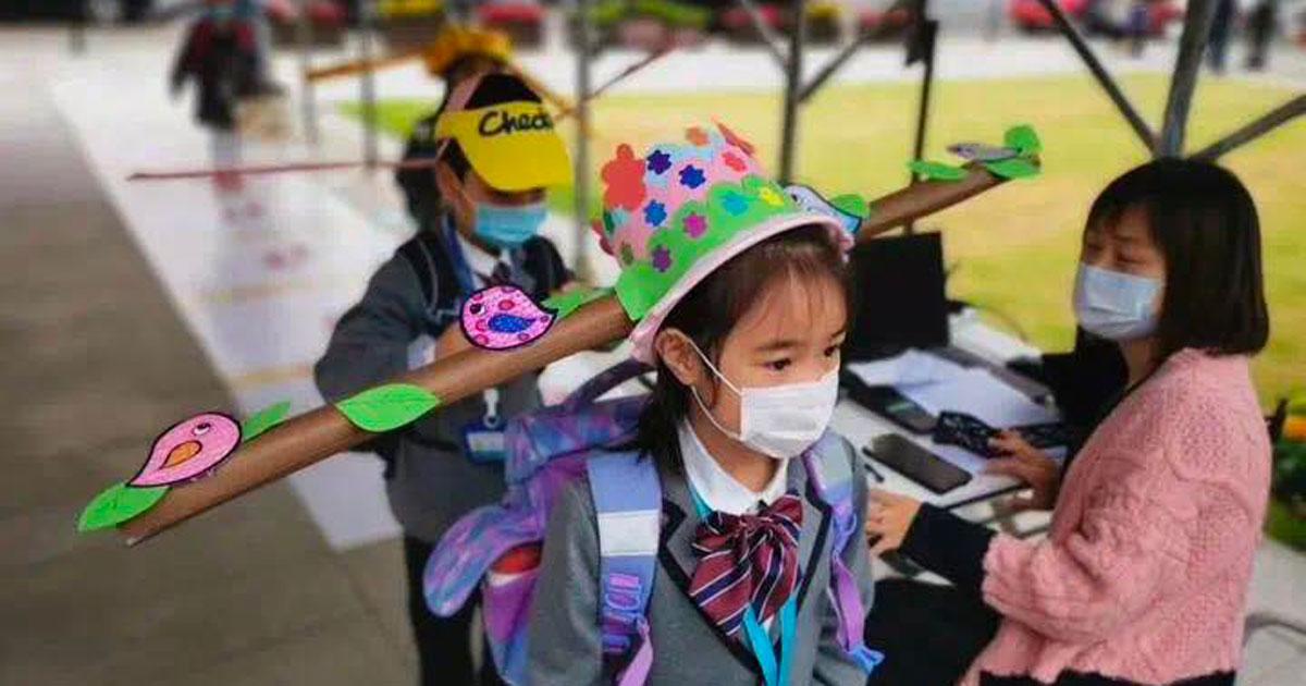 In Cina si torna a scuola: ecco i cappelli usati dai bambini per il distanziamento sociale